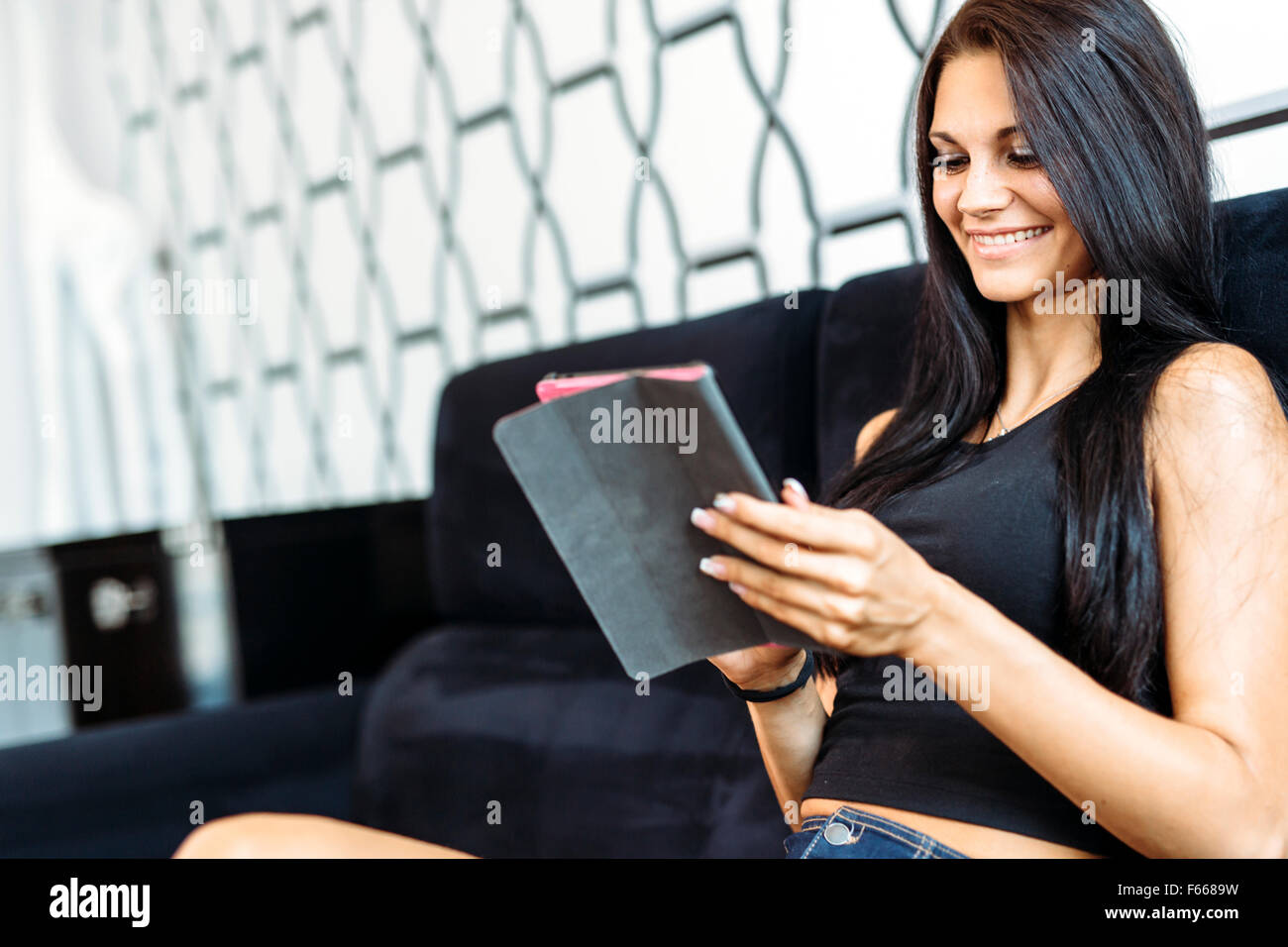 Beautiful happy young woman using a tablet Photo Stock