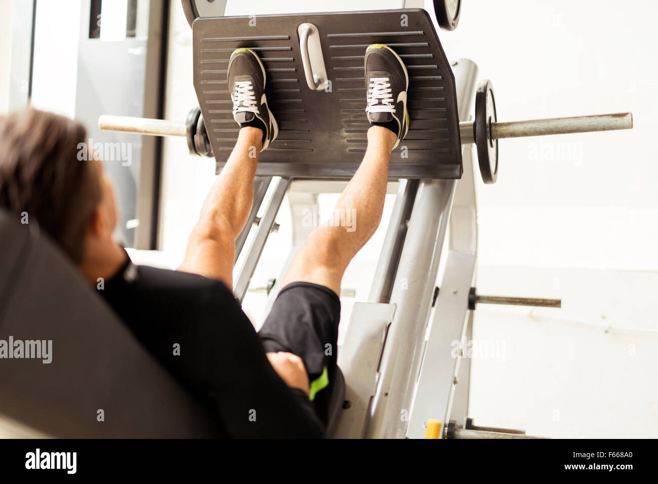 Jeune homme travaillant dans une salle de sport et faire des exercices de jambe Photo Stock