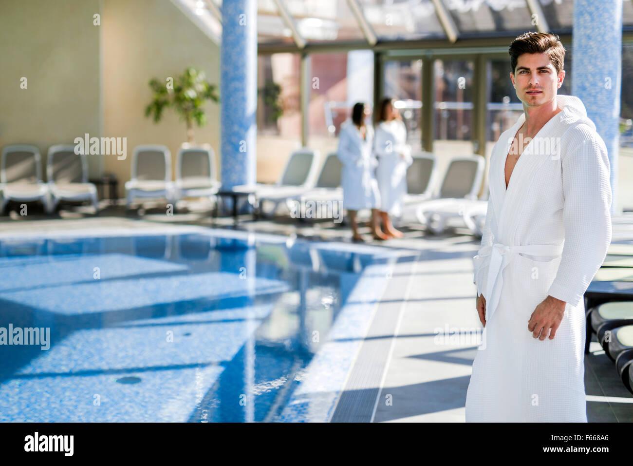 Homme debout à côté d'une piscine dans une robe et relaxant Photo Stock