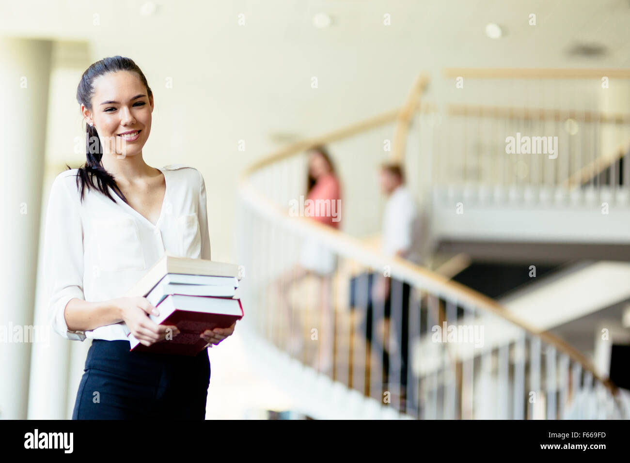 Belle femme holding books et souriant dans une bibliothèque moderne Photo Stock