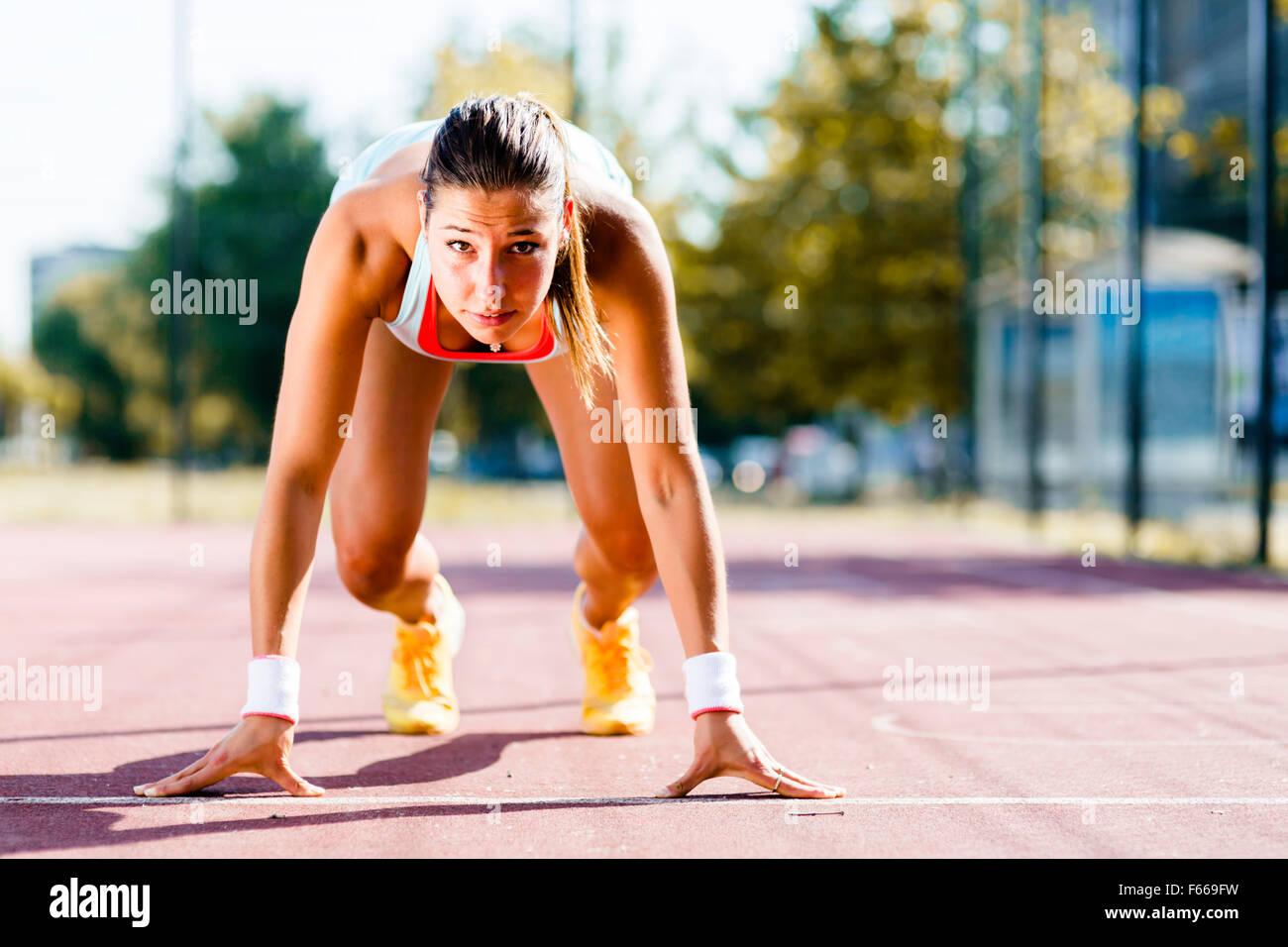 Belle femme sprinter se préparer pour l'exécuter au cours de l'été Photo Stock