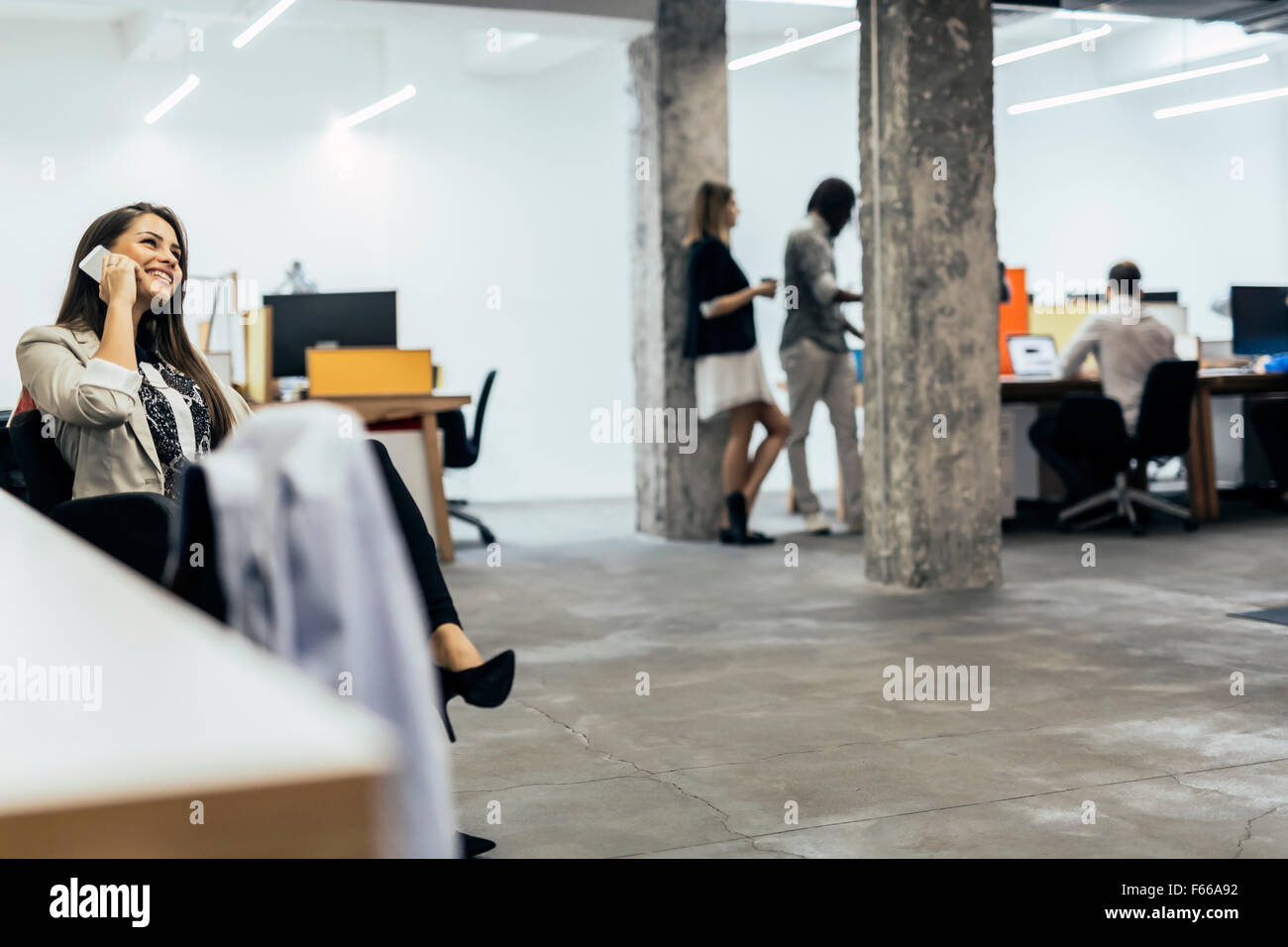 Business Woman using phone in an office Photo Stock