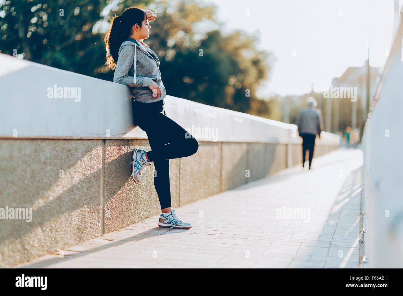 Belle femme se reposant après le jogging en ville Photo Stock