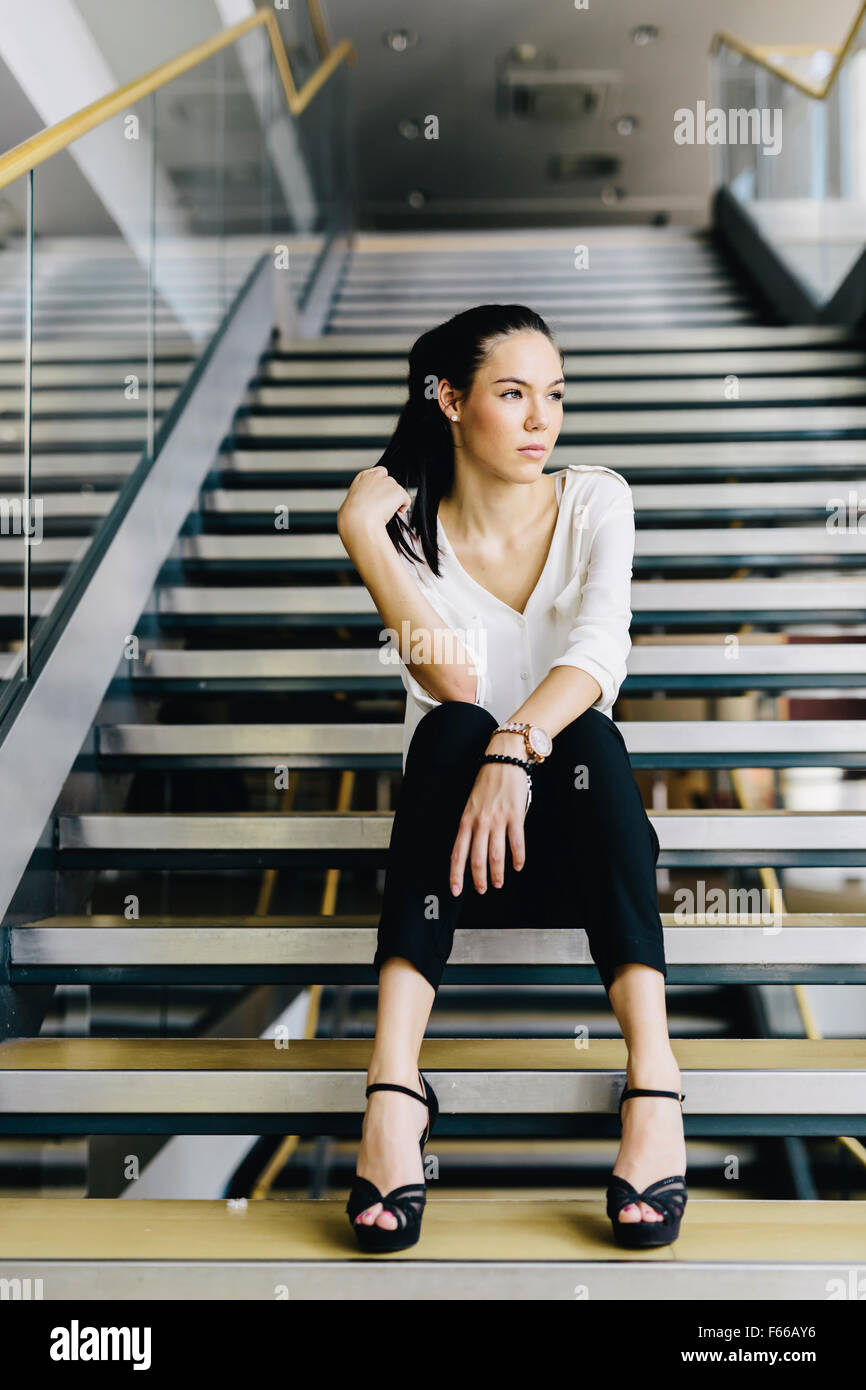 Businesswoman sitting on stairs et la pensée. Photo fashion style Photo Stock