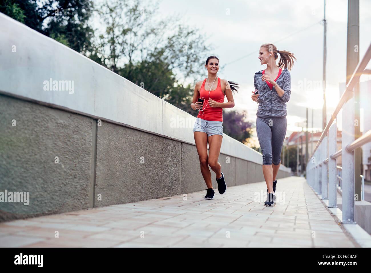 Beau paysage de deux femmes poursuivant leur activité à l'extérieur du jogging dans la ville Photo Stock