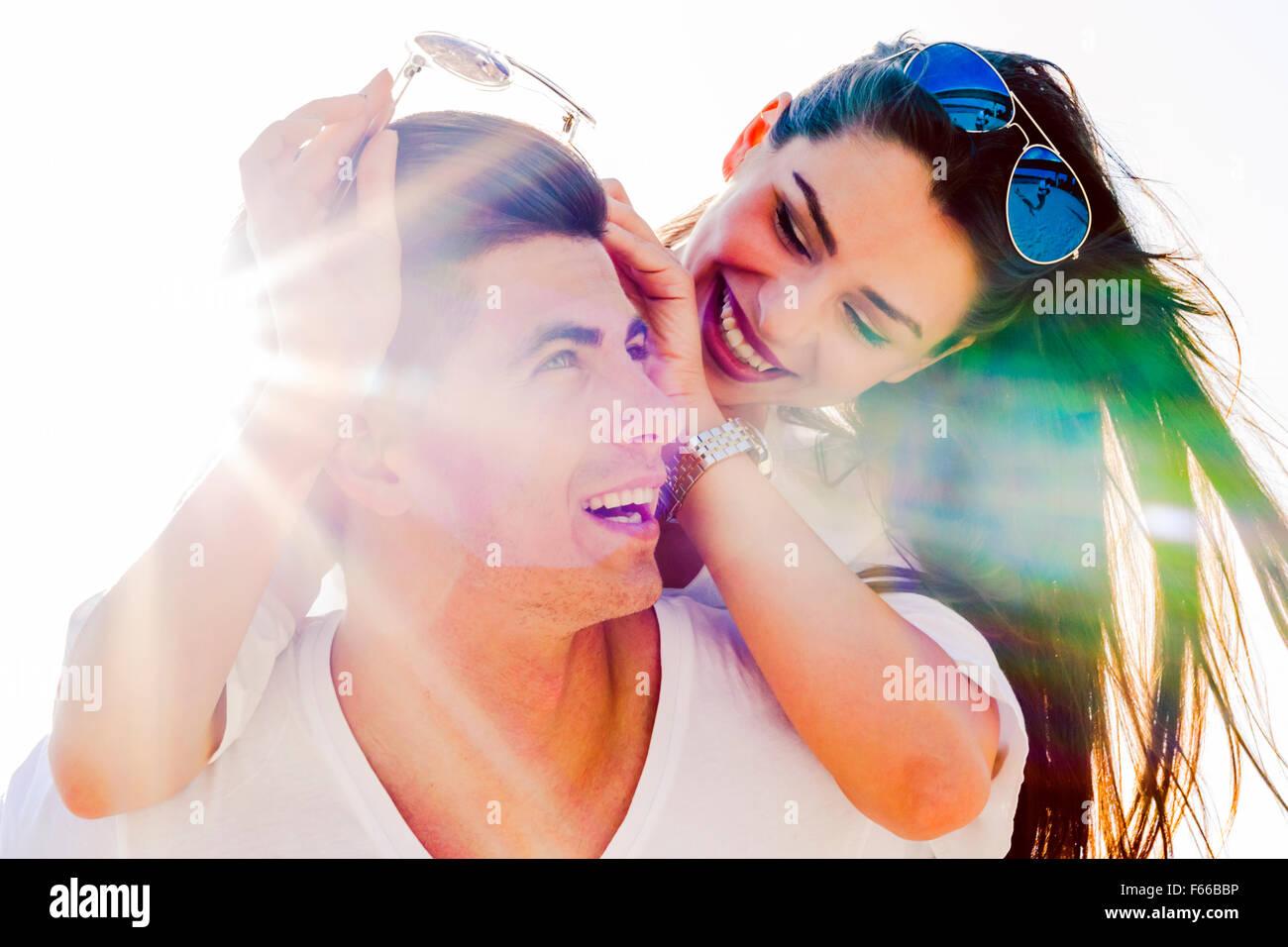 Cheerful handsome man carrying son amie sur le dos sur la plage Photo Stock