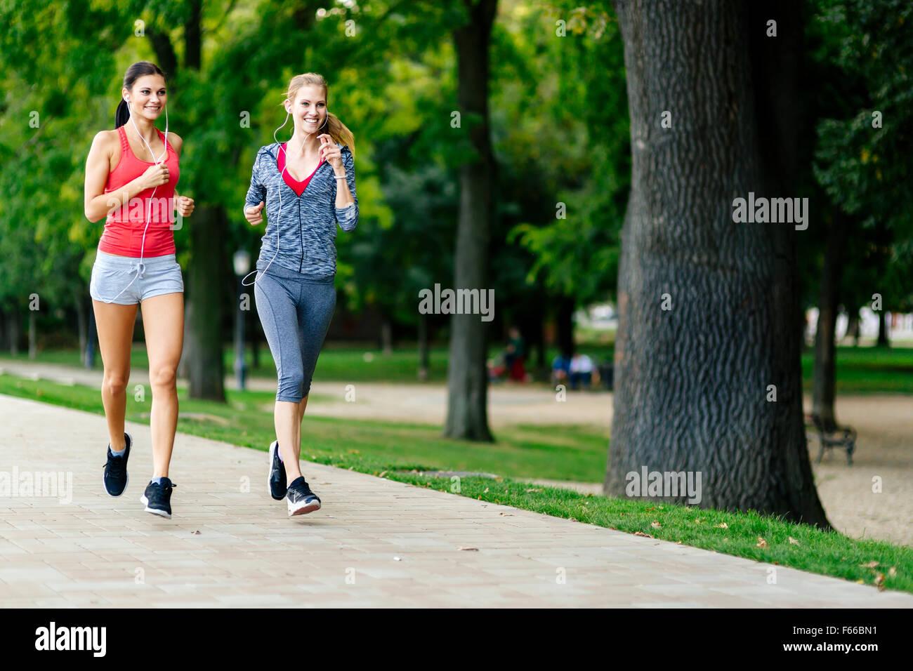 Deux femmes le jogging dans le parc et d'écouter de la musique Banque D'Images