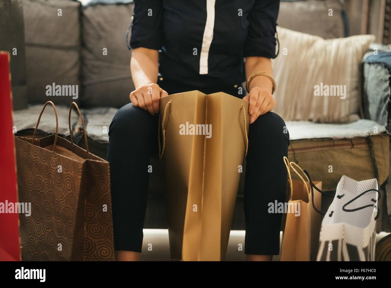 Gros plan sur l'élégante femme assis sur le divan de loft dans purchasings et contrôle de nouveau. Photo Stock
