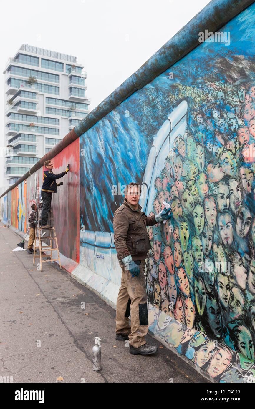 BERLIN, ALLEMAGNE - 30 octobre 2015: Un homme nettoie une murale graffiti off à l'East Side Gallery. Photo Stock