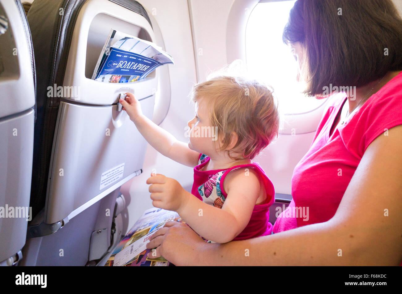 Mère voyageant avec un bébé de l'année dans un avion Photo Stock