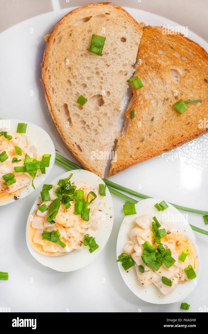 Oeufs durs avec la mayonnaise et la ciboulette en tranches sur la plaque et pain grillé disposées en forme de coeur Banque D'Images