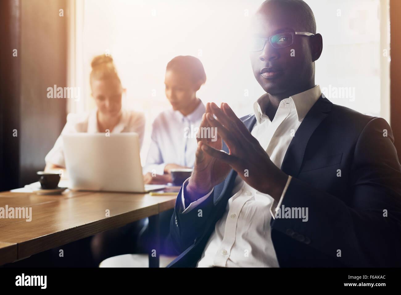 L'homme d'affaires noir grave assis en face de ses employés au bureau Photo Stock