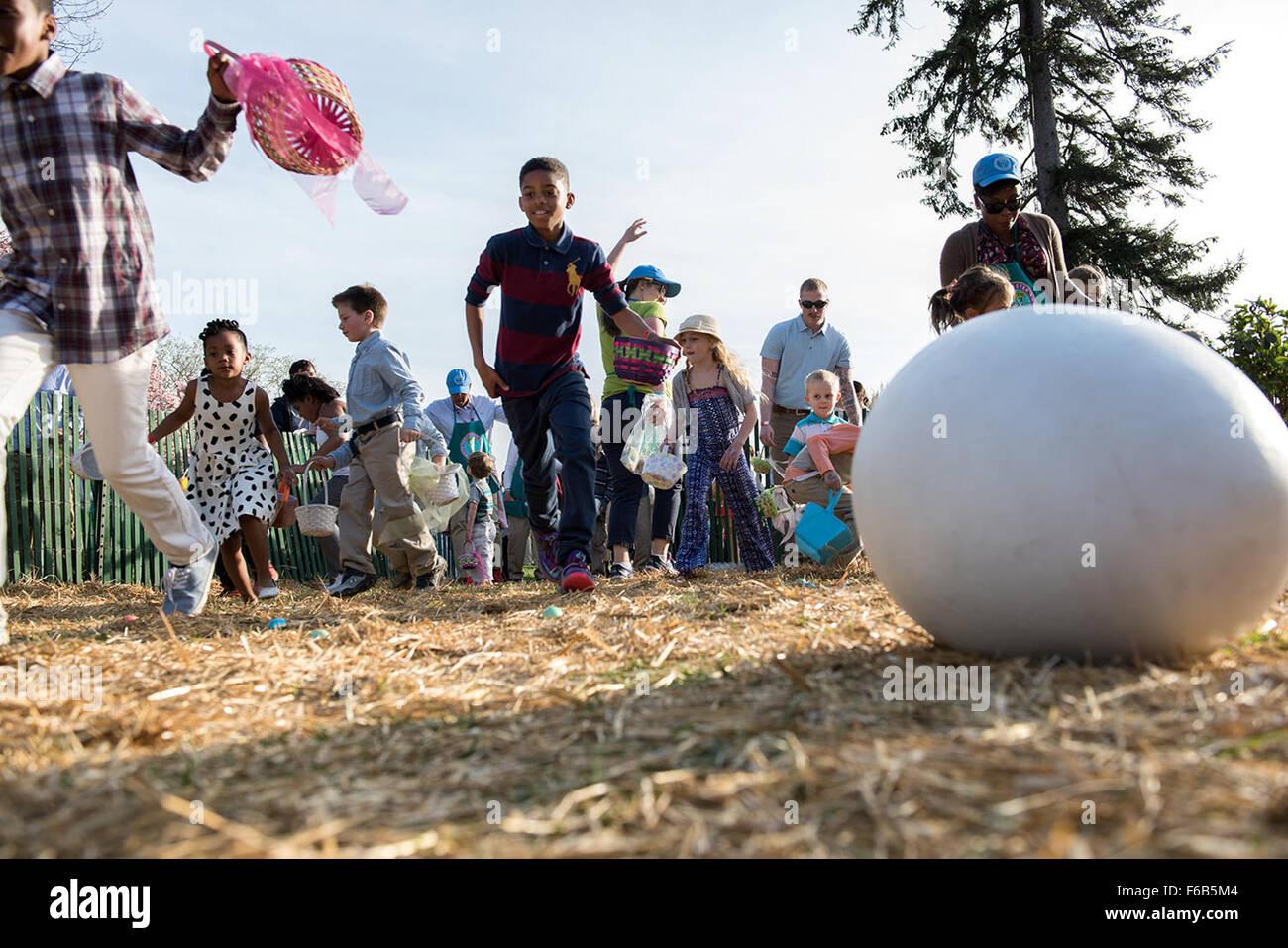 Chasse aux oeufs les enfants au cours de l'assemblée annuelle aux Œufs de Pâques à la Maison Photo Stock