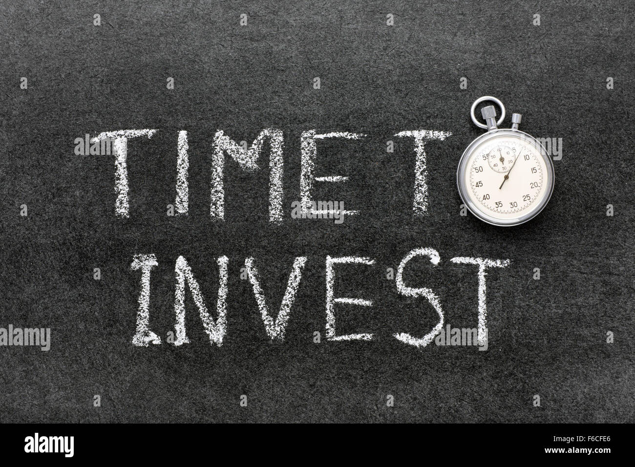 Temps d'investir de phrase à la main sur tableau avec vintage chronomètre précis utilisé Photo Stock