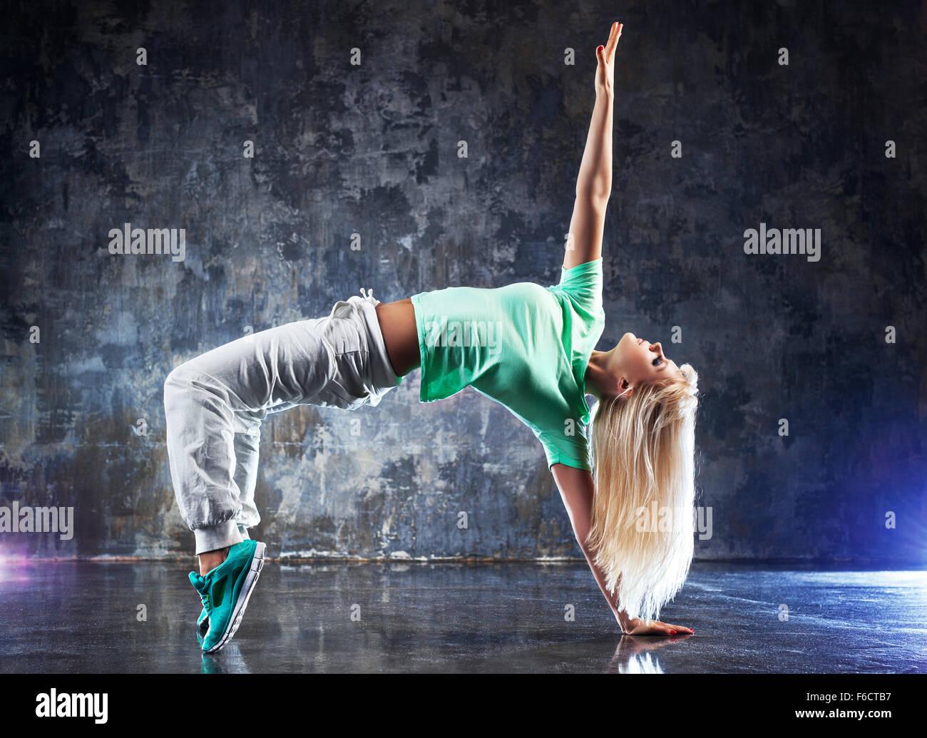 Jeune femme danseuse moderne. Sur fond de murs en pierre sombre. Photo Stock