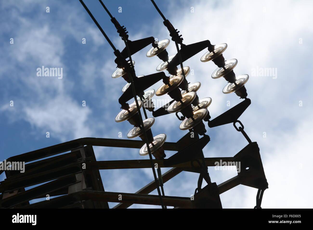 Les connecteurs de câble à haute tension et isolateurs de verre contre le ciel bleu avec des nuages Photo Stock