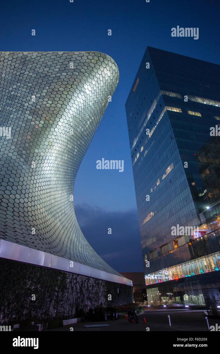 Les courbes de l'Soumaya Museum of Art contraste avec un haut bâtiment moderne de la ville de Mexico, Mexique. Photo Stock