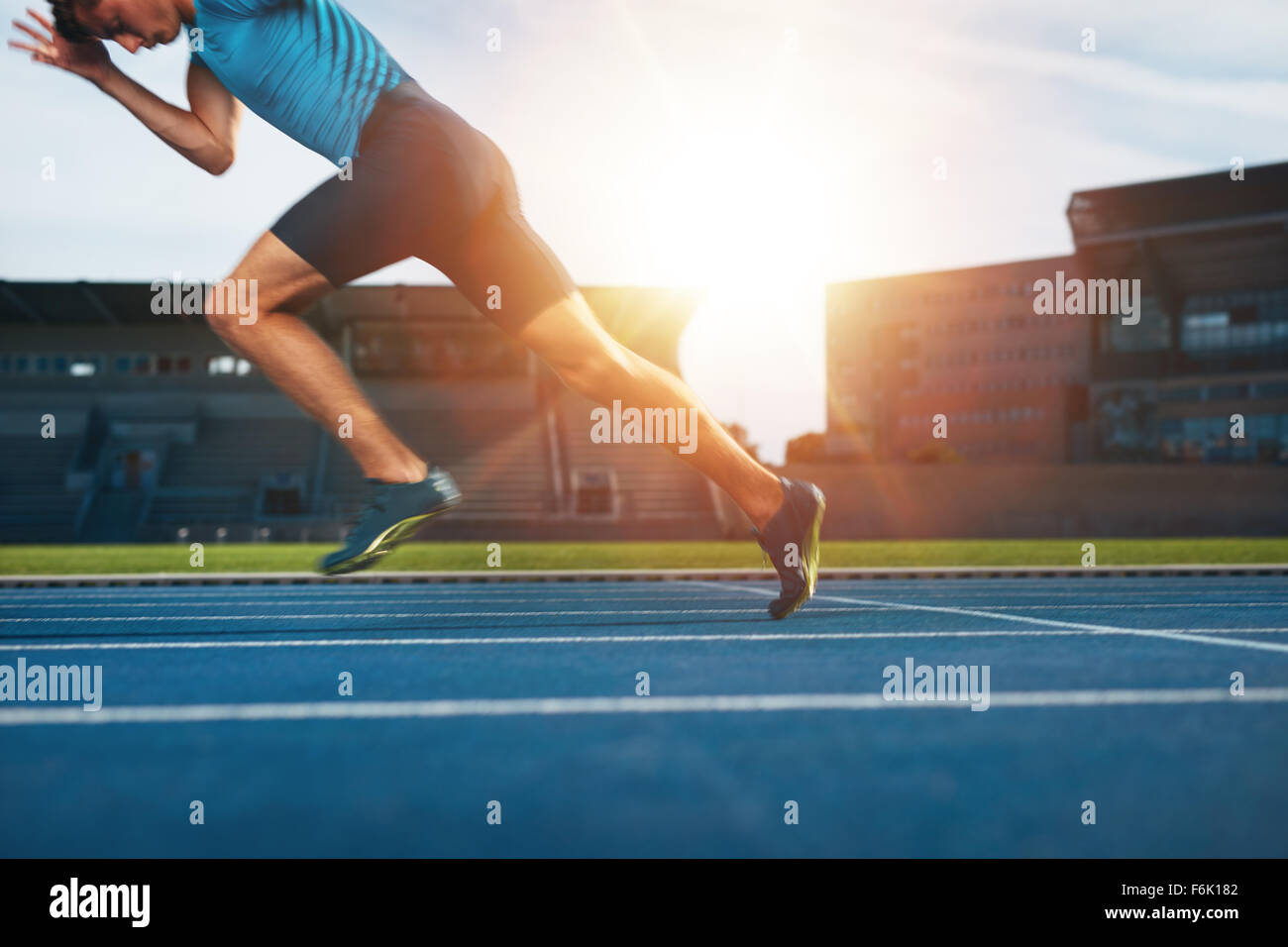 Coup de jeune athlète masculin de lancer au large de la ligne de départ dans une course. Runner s'exécutant Photo Stock