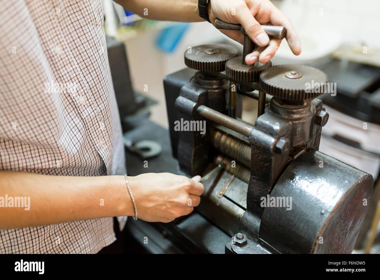 Goldsmith de l'utilisation de la machine pour faire plus mince en métal Photo Stock