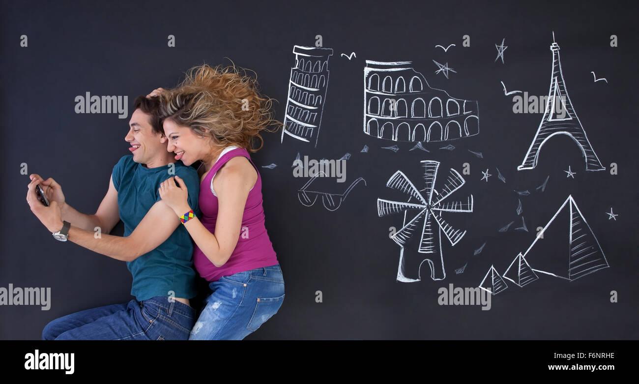 Jeune couple faisant un avec selfies attractions monde ilustrations derrière. Photo Stock