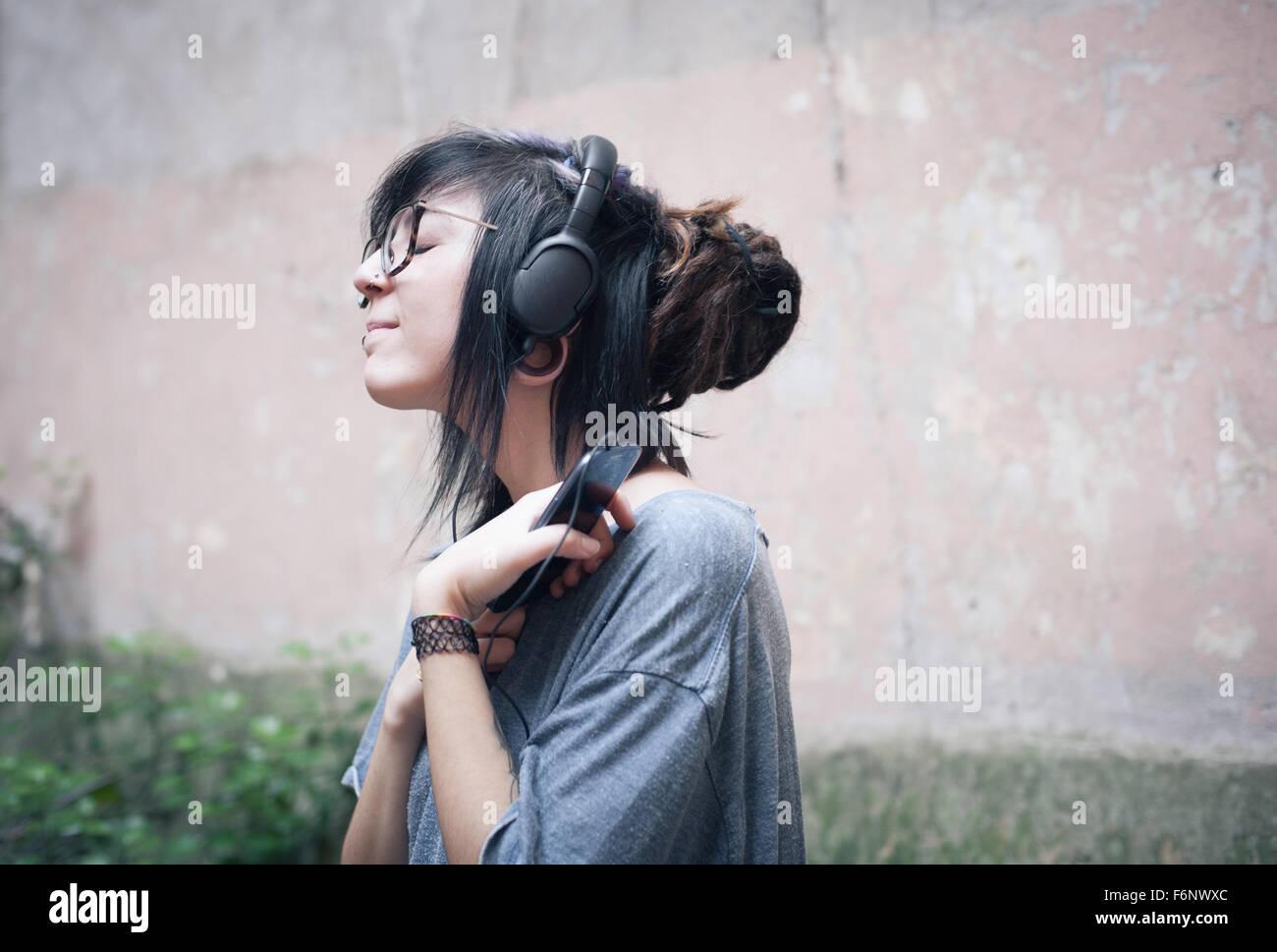 Femme de l'adolescence avec un casque à l'écoute de la musique avec une profonde émotion Photo Stock