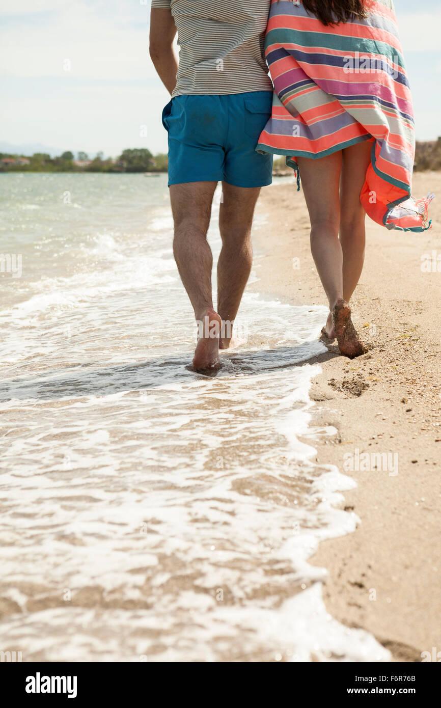 Jeune couple walking along beach Banque D'Images