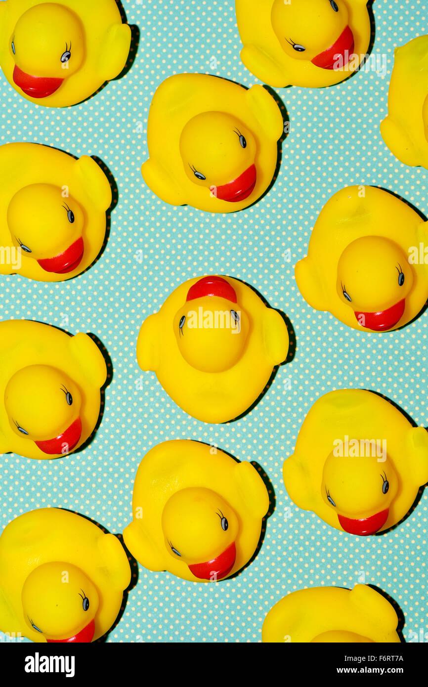 Un tas de canards en caoutchouc, l'un d'entre eux, à contre-courant sur un fond à motifs de points, Photo Stock
