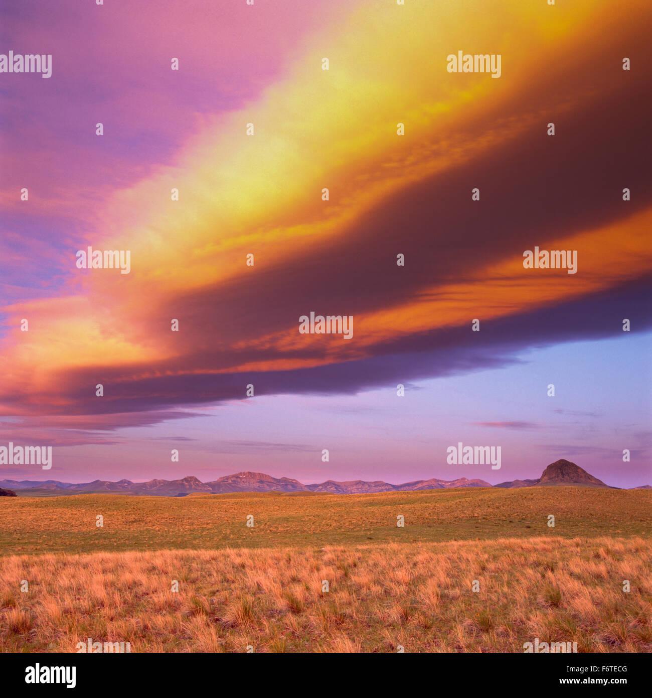 Lever du soleil nuages sur prairie et botte butte rocheuses le long de près de augusta, Montana Photo Stock