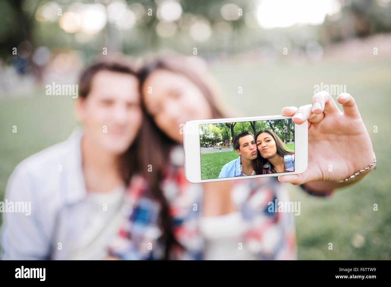 Sur l'affichage de photos d'un smartphone de young couple in love Photo Stock