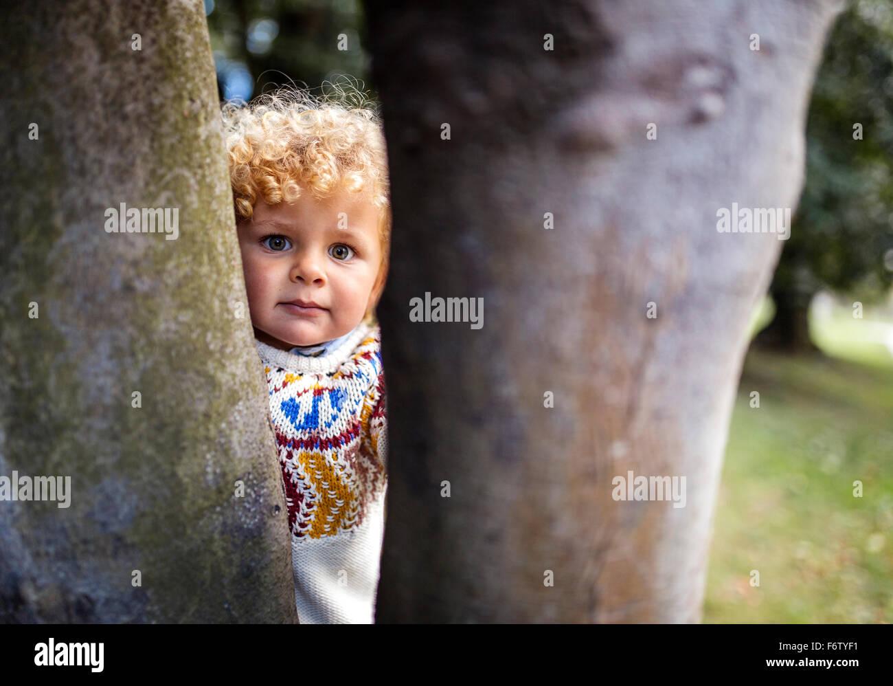 Portrait de petit garçon blond portant pull tricoté à motifs à entre deux troncs d'arbre Photo Stock