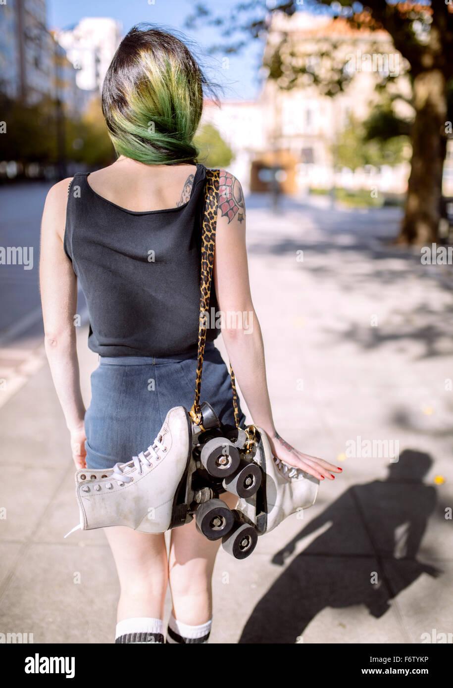 L'Espagne, Gijon, vue arrière de jeune femme aux cheveux teints vert portant des patins sur épaule Banque D'Images