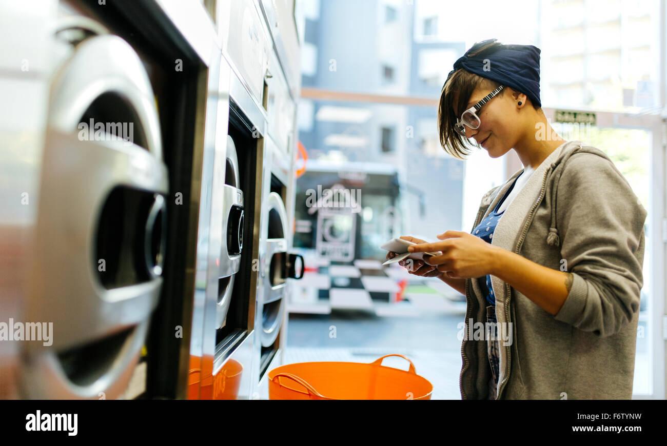 Jeune femme lire quelque chose dans une laverie Photo Stock
