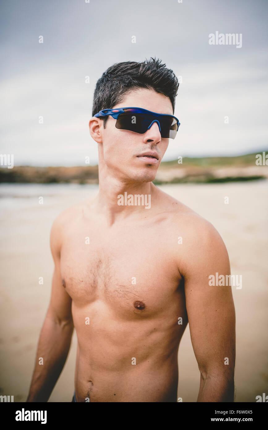 01a90ad3d68807 Portrait de jeune homme torse nu sur la plage le port de lunettes de soleil