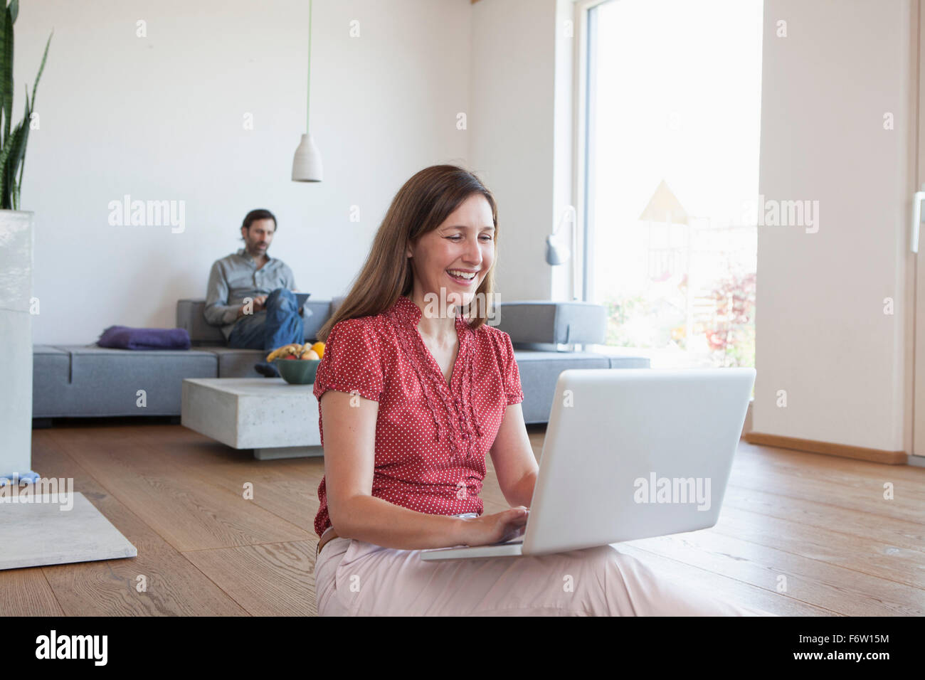 Mature Woman using laptop on floor in living room, man using digital tablet in background Photo Stock