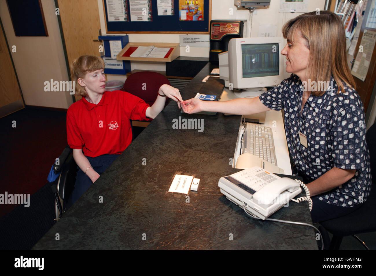 Laccès aux services réceptionniste et femme handicapée au gymnase