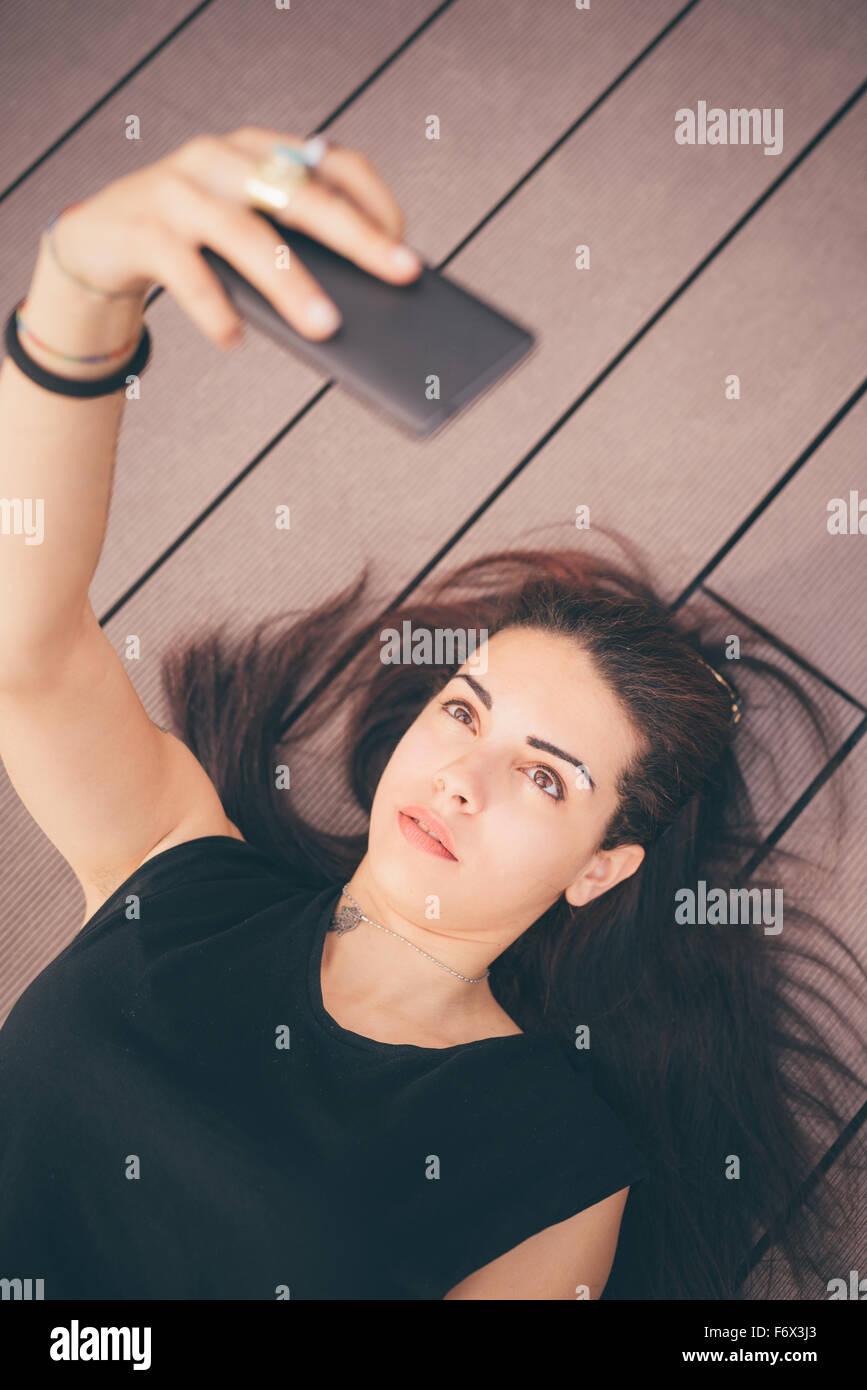 De beaux cheveux bruns rougeâtres caucasian girl couché sur un trottoir à l'aide d'un smartphone Photo Stock
