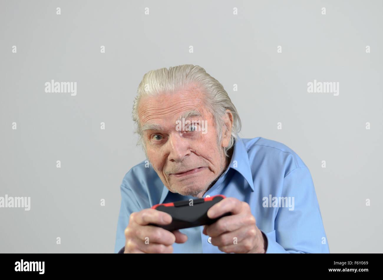 Drôle homme âgé ou grand-père jouer à un jeu vidéo sur console, portrait avec copie Photo Stock