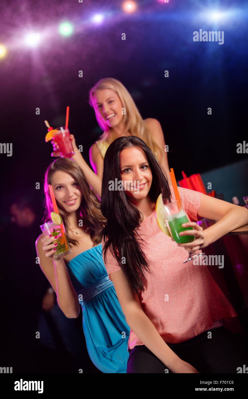 Groupe d'amis au bar élever leur verre de cocktals Banque D'Images