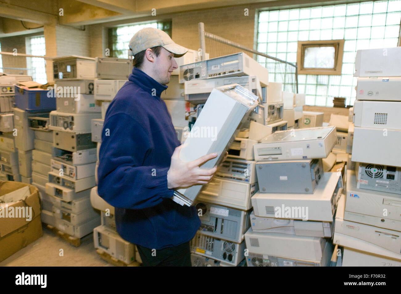 L'homme s'empilent les ordinateurs usés à l'usine de recyclage, Photo Stock