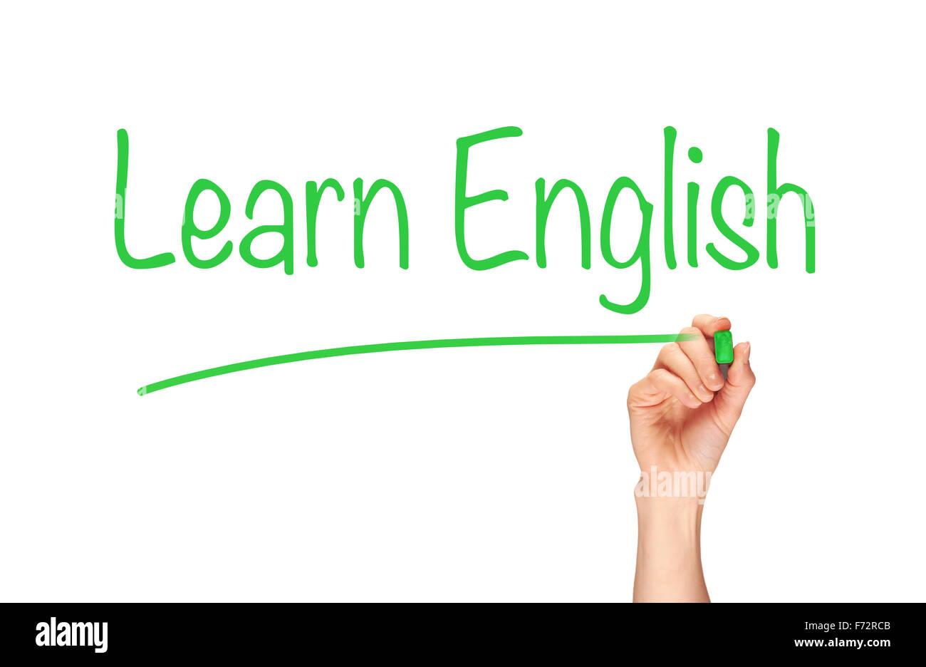 A woman's hand writing the word, apprendre l'anglais, sur un écran clair. Photo Stock