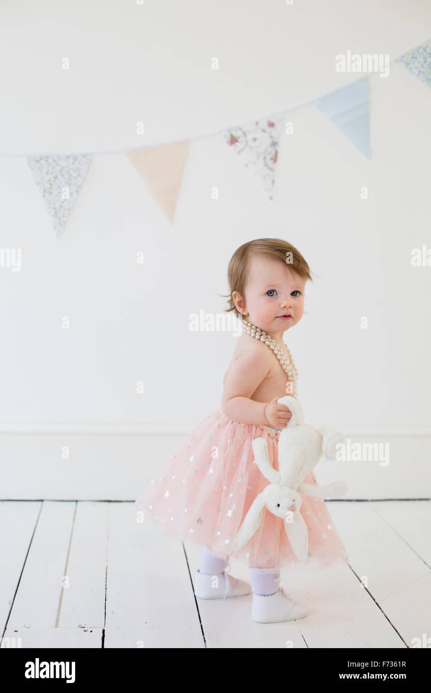 Jeune fille tenant une peluche, debout dans un studio de photographes, posant pour une photo. Photo Stock