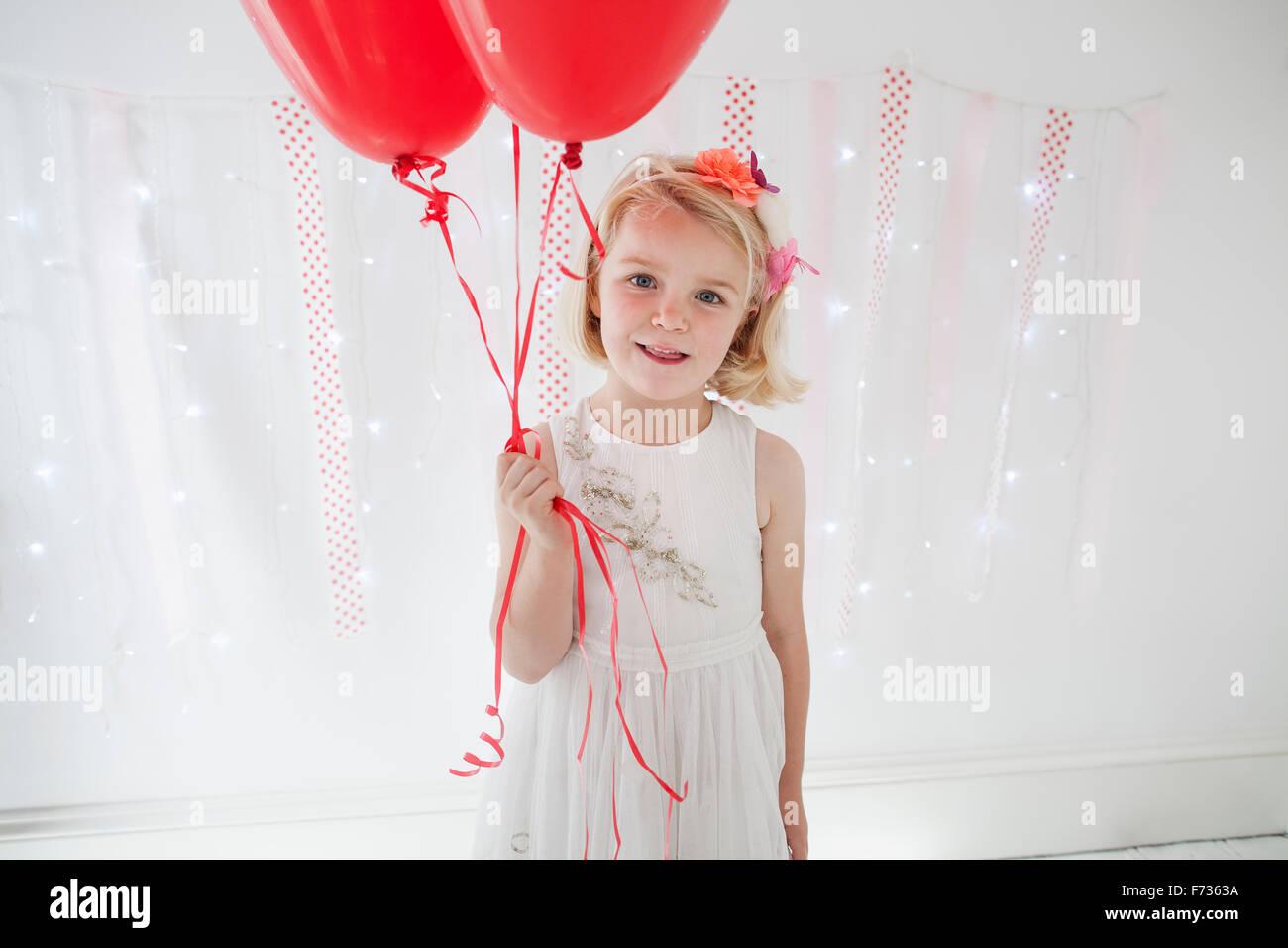 Jeune fille posant pour une photo dans un studio de photographes, holding red balloons. Photo Stock