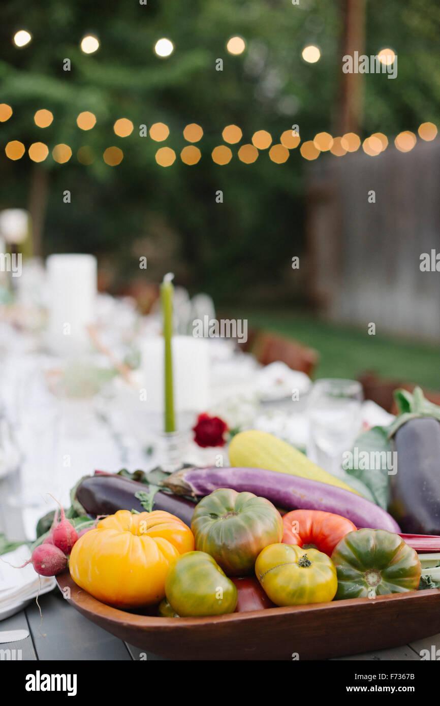 Longue table avec des assiettes et des verres, de l'alimentation et des boissons dans un jardin, un bol de légumes Photo Stock