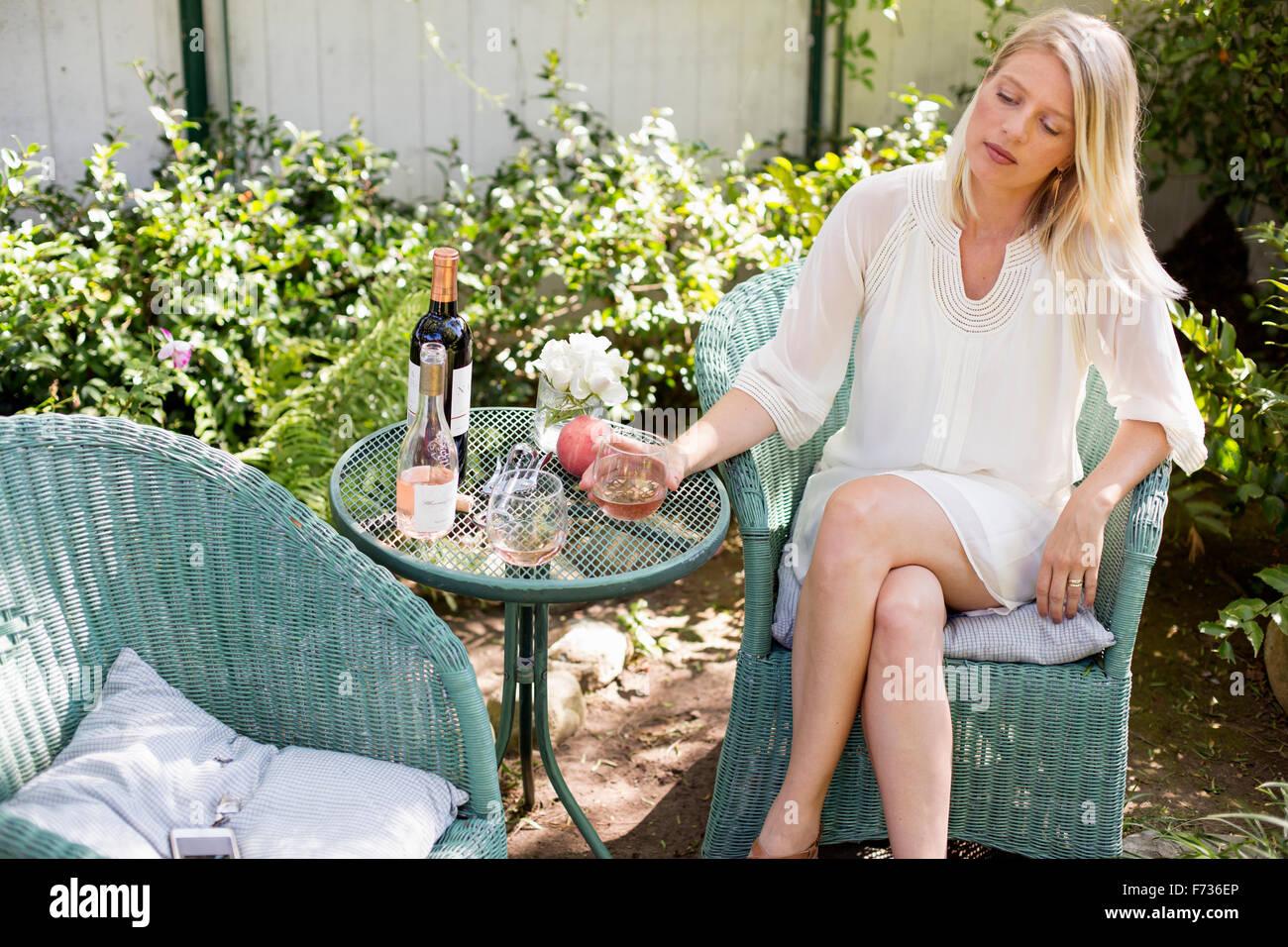 Femme blonde assise dans un fauteuil en osier dans un jardin avec un verre de vin. Photo Stock