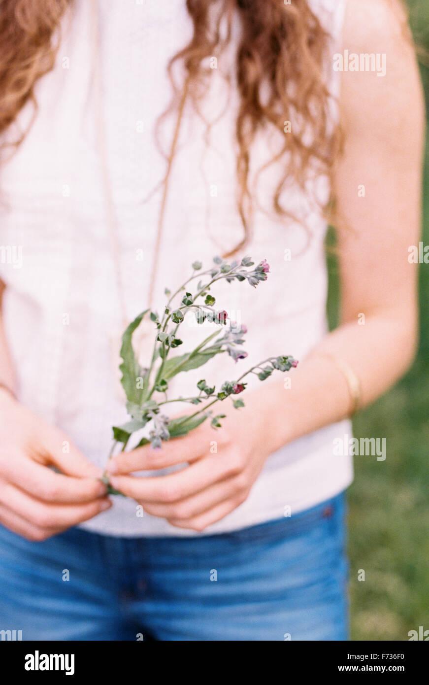 Portrait d'une femme tenant une fleur sauvage. Banque D'Images
