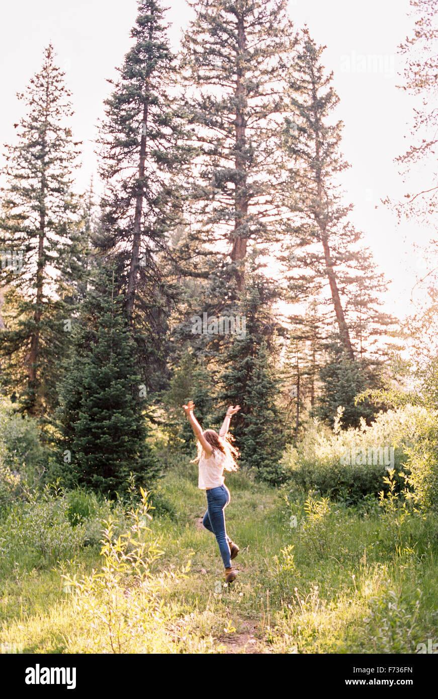Femme sautant de joie dans une forêt ensoleillée. Photo Stock