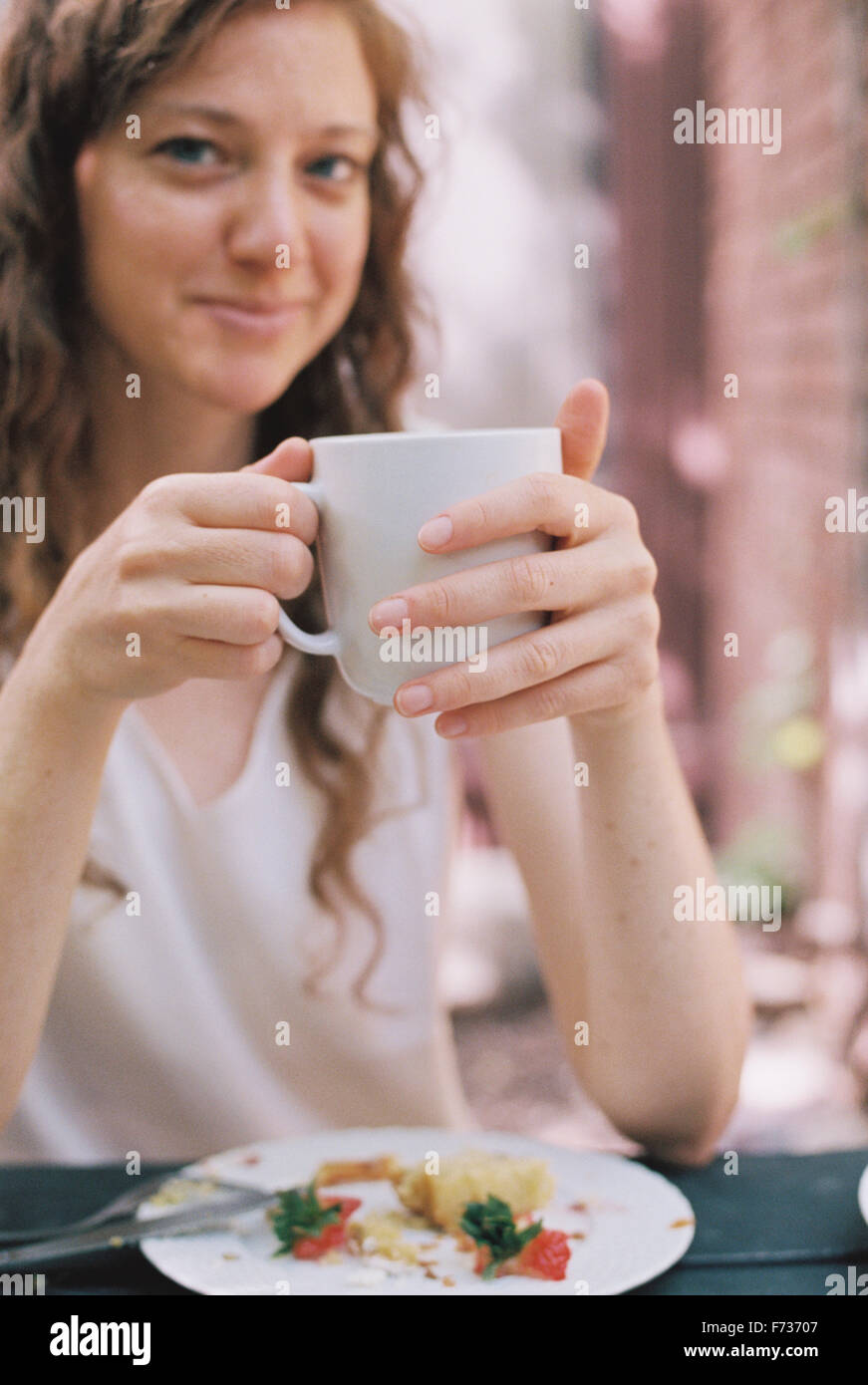 Smiling woman holding a white chine tasse de thé. Photo Stock