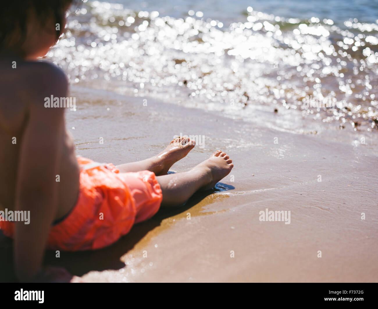 Un garçon assis sur le sable au bord de l'eau regardant les vagues à la plage. Photo Stock