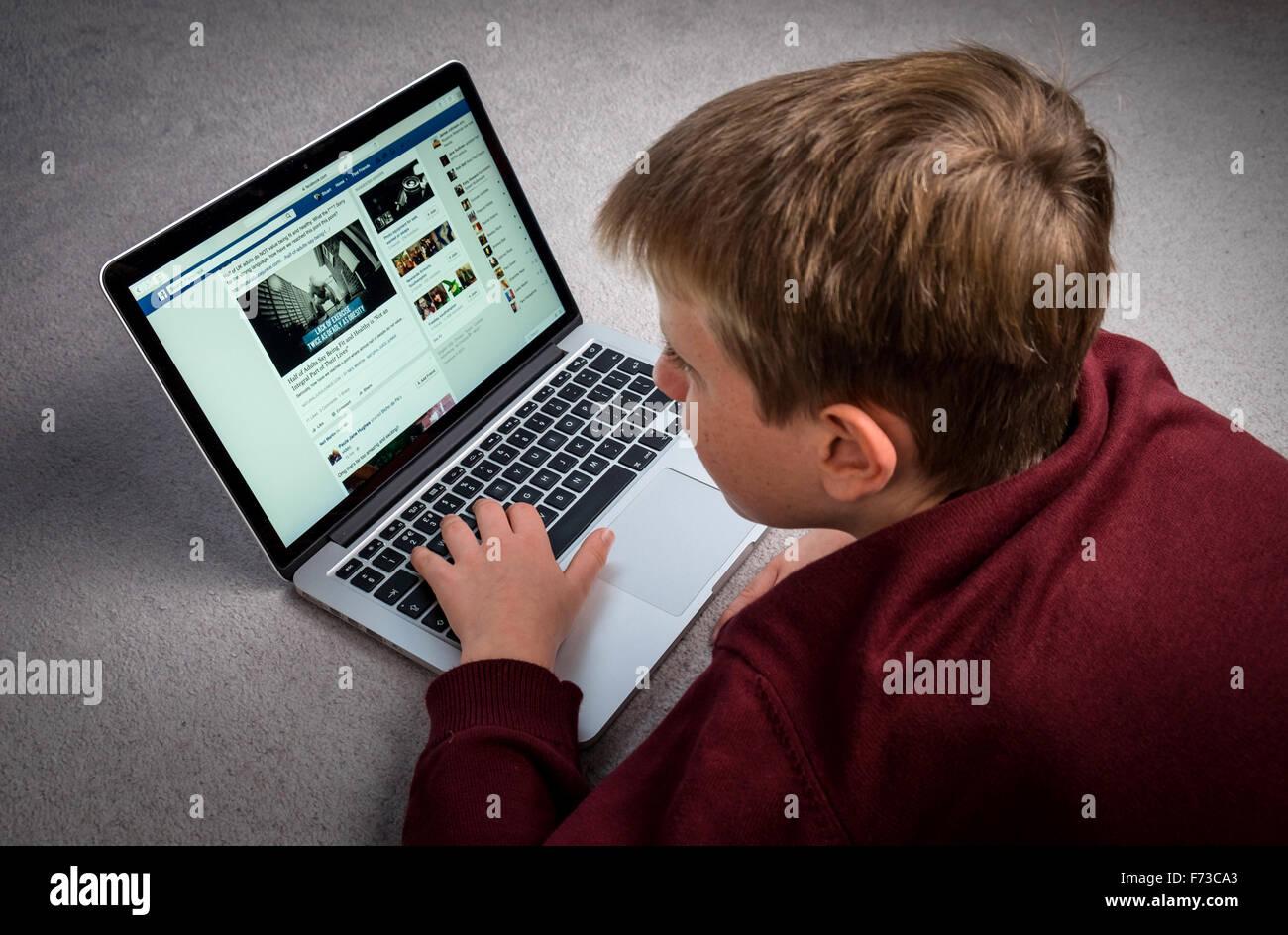 Un garçon à la recherche à Facebook sur un ordinateur portable Photo Stock