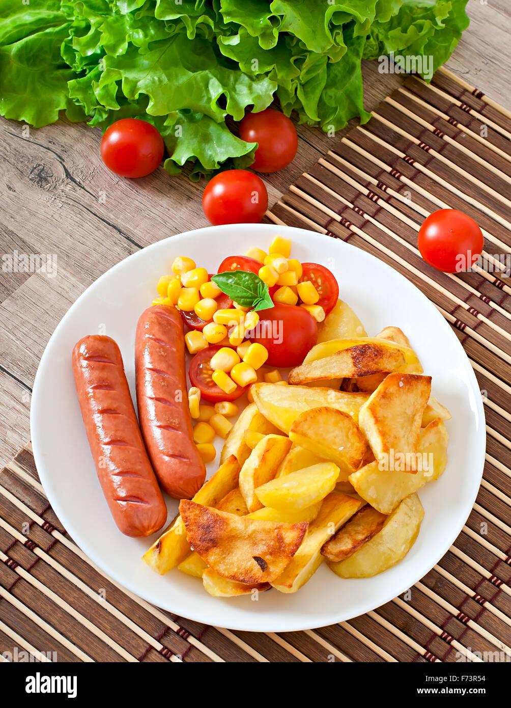 Saucisse avec des pommes de terre sautées et des légumes sur une plaque Photo Stock